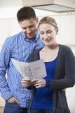 Coppie felici che esaminano i dettagli per la proprietà che sperano di comprare Fotografia Stock Libera da Diritti