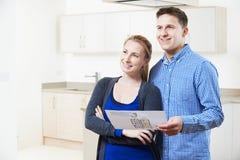Coppie felici che esaminano i dettagli per la proprietà che sperano di comprare Immagini Stock
