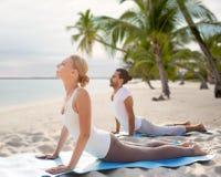 Coppie felici che fanno gli esercizi di yoga sulla spiaggia fotografia stock libera da diritti