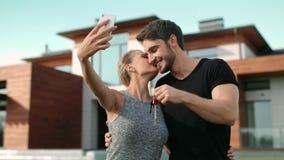 Coppie felici che fanno la foto del selfie con le chiavi della casa fuori della residenza stock footage