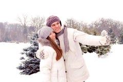 Coppie felici che fanno selfie ad una data in parco nell'inverno Immagini Stock Libere da Diritti