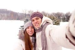 Coppie felici che fanno selfie ad una data in parco nell'inverno Immagine Stock Libera da Diritti