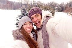 Coppie felici che fanno selfie ad una data in parco nell'inverno Fotografia Stock Libera da Diritti