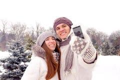 Coppie felici che fanno selfie ad una data in parco nell'inverno Immagine Stock