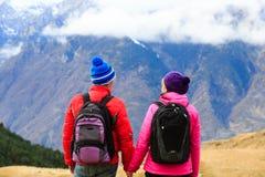 Coppie felici che fanno un'escursione in montagne sceniche Fotografie Stock