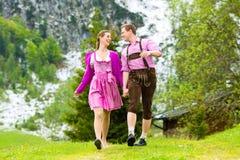 Coppie felici che fanno un'escursione nel prato alpino fotografia stock libera da diritti