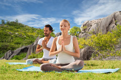 Coppie felici che fanno yoga e che meditano all'aperto Immagine Stock Libera da Diritti