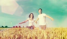 Coppie felici che funzionano sopra il grainfield fotografia stock libera da diritti