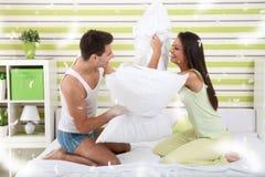 Coppie felici che giocano con i cuscini a letto fotografia stock