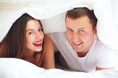 Coppie felici che giocano nell'ambito della copertura del piumino alla camera da letto fotografia stock