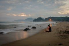Coppie felici che godono dei loro momenti sulla spiaggia di Karang Hawu, Java ad ovest, Indonesia immagini stock