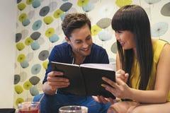 Coppie felici che guardano media sociali in un taccuino alla barra Immagini Stock Libere da Diritti