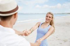 Coppie felici che hanno divertimento sulla spiaggia Fotografie Stock