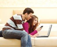 Coppie felici che lavorano al computer portatile Immagini Stock