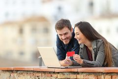 Coppie felici che pagano online con la carta di credito ed il computer portatile immagine stock