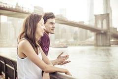 Coppie felici che parlano nella parte anteriore il ponte di Brooklyn famoso immagine stock libera da diritti
