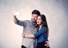 Coppie felici che prendono selfie con la chiara parete Fotografie Stock Libere da Diritti