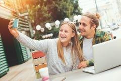 Coppie felici che prendono selfie mentre sedendosi in caffè all'aperto fotografia stock libera da diritti
