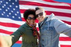 Coppie felici che prendono selfie sopra la bandiera americana Fotografia Stock