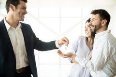 Coppie felici che ricevono le chiavi dal mediatore In New Apartment fotografia stock