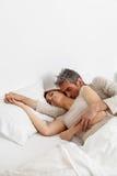 Coppie felici che riposano nel letto Immagine Stock