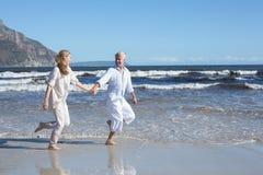 Coppie felici che saltano a piedi nudi sulla spiaggia Fotografie Stock Libere da Diritti