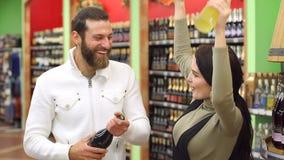 Coppie felici che scelgono il champagne ed il liquore nel deposito di vino, ballano e ridono video d archivio