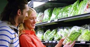 Coppie felici che selezionano le verdure nella sezione organica stock footage