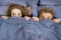 Coppie felici che si nascondono sotto la coperta a letto Coppie in camera da letto di mattina immagine stock