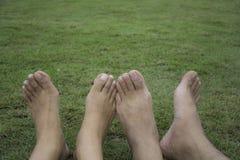 Coppie felici che si rilassano sull'erba verde Coppie che si trovano sull'erba esterna barefoot Maschio e femmina asiatici fotografia stock