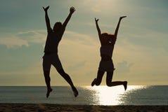 Coppie felici che si rilassano sulla spiaggia all'alba, vista posteriore fotografie stock