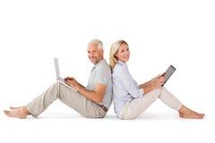Coppie felici che si siedono facendo uso del pc della compressa e del computer portatile Immagini Stock