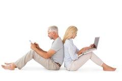 Coppie felici che si siedono facendo uso del pc della compressa e del computer portatile Fotografia Stock