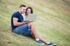 Coppie felici che si siedono nel parco con il computer portatile Immagine Stock