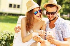 Coppie felici che si siedono su un banco con gli smartphones Fotografia Stock