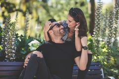 Coppie felici che si siedono sul banco che se esamina immagini stock