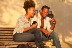 Coppie felici che si siedono sul banco fuori con il telefono cellulare e lo spuntino fotografie stock