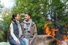 Coppie felici che si siedono sul banco vicino al fuoco del campo Fotografie Stock