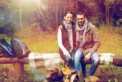 Coppie felici che si siedono sul banco vicino al fuoco del campo Fotografie Stock Libere da Diritti