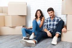 Coppie felici che si siedono sul pavimento intorno alle scatole dopo l'acquisto della casa Fotografie Stock