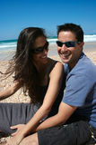 Coppie felici che si siedono sulla spiaggia Immagini Stock Libere da Diritti
