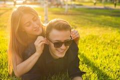 Coppie felici che si trovano sull'erba e che riposano insieme, divertiresi all'aperto Ritratto degli amanti divertenti Fotografia Stock