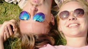 Coppie felici che si trovano sull'erba in occhiali da sole e che si tengono per mano, riflessione del cielo video d archivio