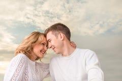 Coppie felici che sorridono e che guardano uno un altro sotto la SK soleggiata Immagini Stock Libere da Diritti