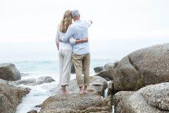 Coppie felici che stanno sulla roccia e che esaminano il mare Fotografie Stock Libere da Diritti