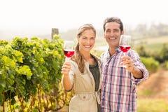 Coppie felici che tengono i bicchieri di vino Immagini Stock