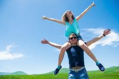 Coppie felici con a braccia aperte, ragazza che si siede sull'uomo delle spalle Immagini Stock