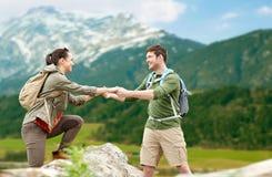 Coppie felici con gli zainhi che viaggiano in altopiani Immagine Stock Libera da Diritti