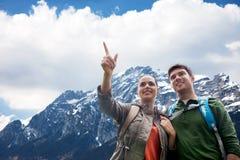 Coppie felici con gli zainhi che viaggiano in altopiani Immagine Stock