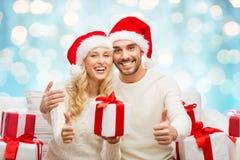 Coppie felici con i regali ed i pollici di natale su Fotografie Stock Libere da Diritti